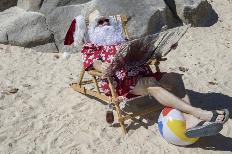 Santa Claus, die unter Verwendung des Reflektors sich bräunt stockfoto