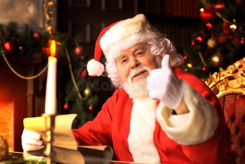 Santa Claus die zich met omhoog duimen bevinden De Decoratie van het huis stock foto's