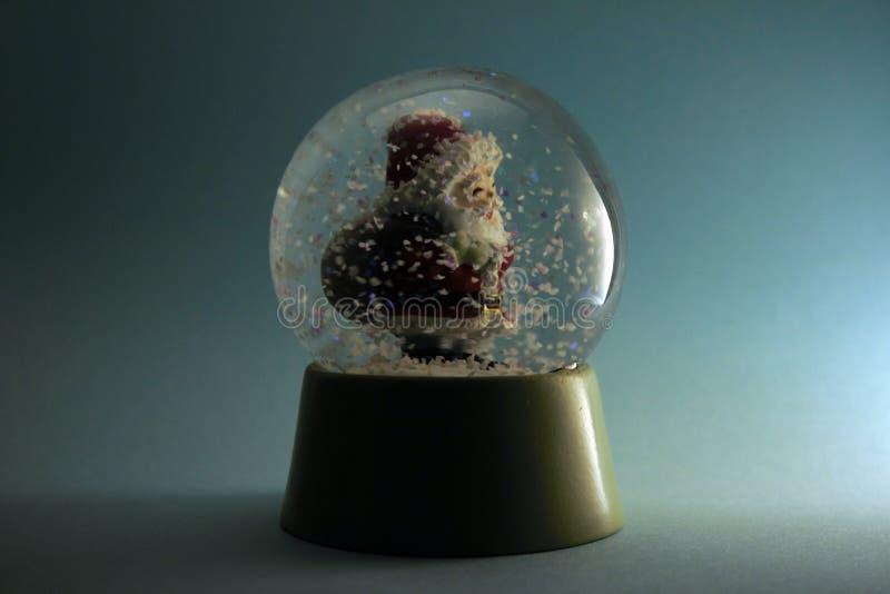 Santa Claus die zijn zak in een sneeuwstormbol dragen op blauwe achtergrond royalty-vrije stock afbeelding