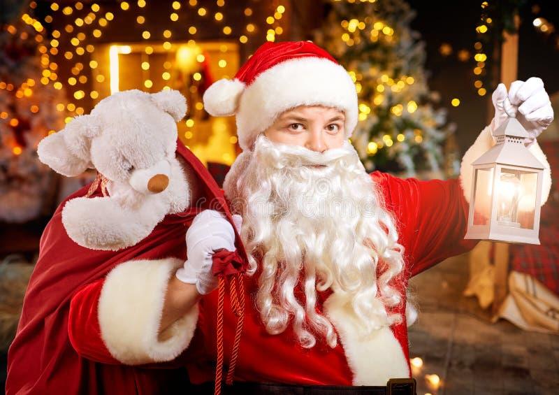 Santa Claus divertida con un bolso en su mano en un cuarto con un firepl fotografía de archivo