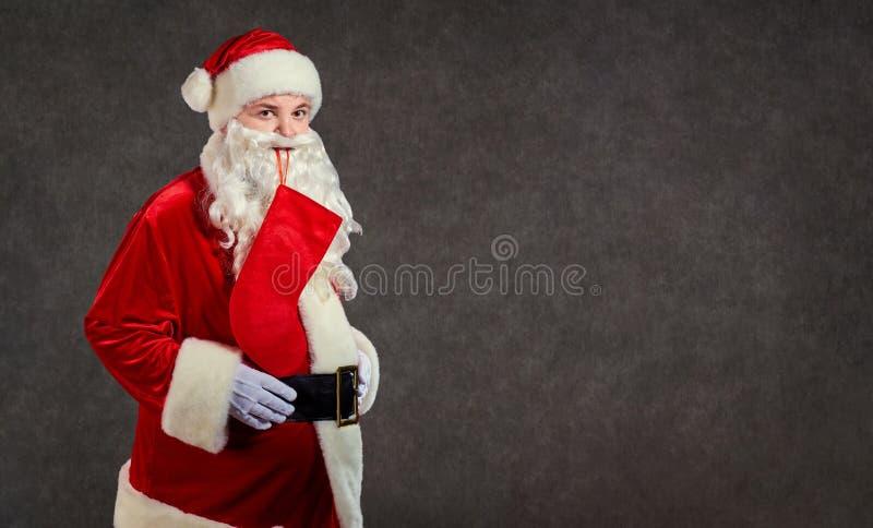 Santa Claus divertida feliz con el calcetín rojo en fondo fotografía de archivo libre de regalías