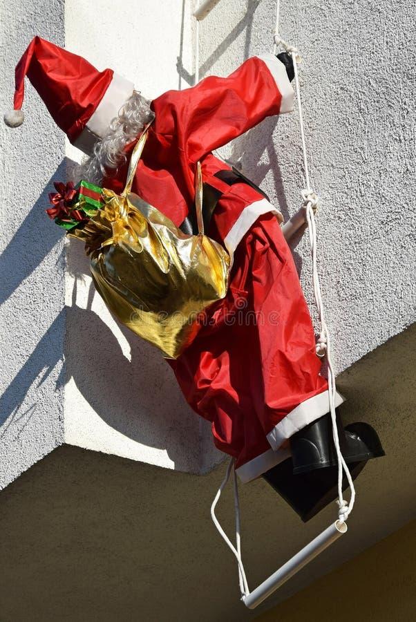 Santa Claus docka som kl?ttrar en stege royaltyfria bilder