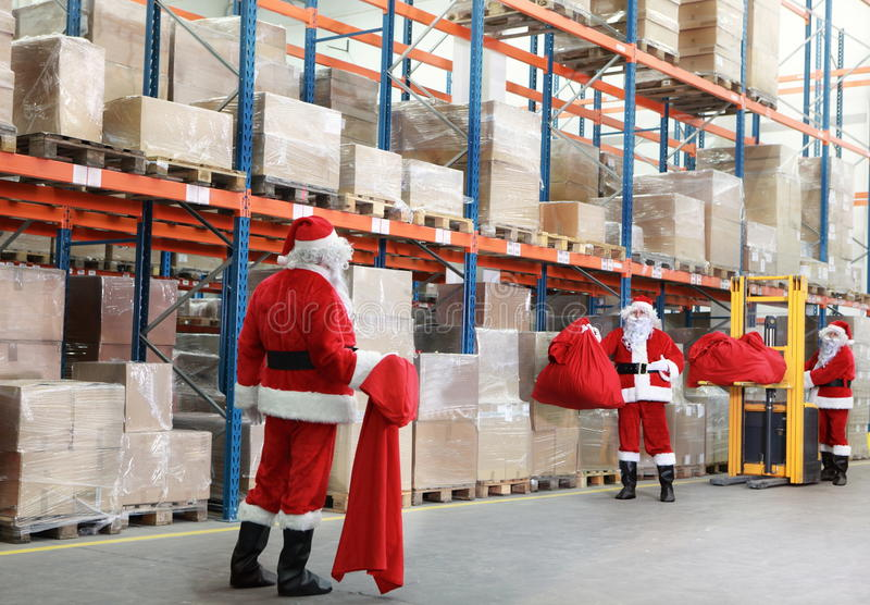 Santa claus doing wholesale shopping. Santa claus with empty red sack searching for gifts in the large storehouse royalty free stock photo