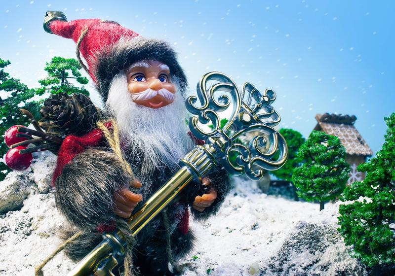 Santa Claus doll with big toy key. Christmas composition with Santa Claus doll holding a key and bag with presents on winter nature background royalty free stock images