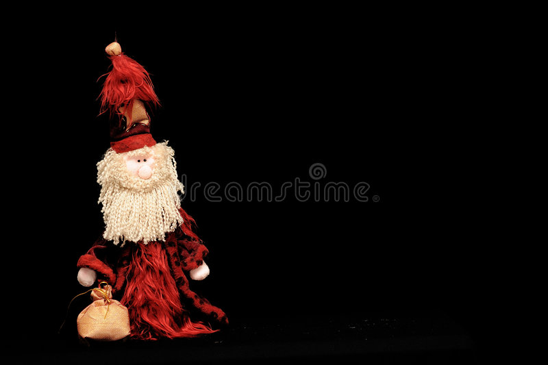 Santa Claus doll on black. A view of a Santa Claus doll wearing a red robe, white beard and red hat, carrying a sack, isolated on a black background stock images