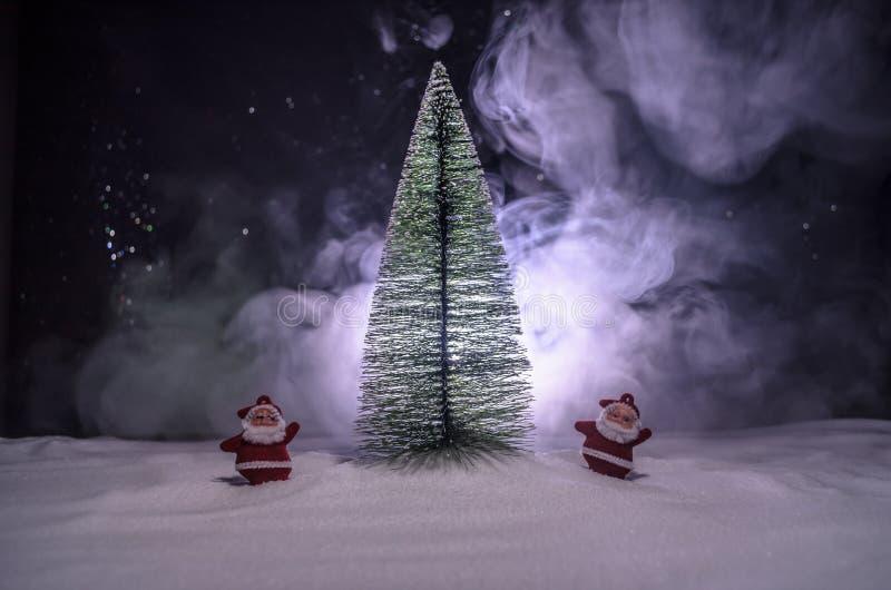 Santa Claus Doll feliz el tiempo de la Navidad con el árbol y la nieve Fondo colorido del bokeh Higo del modelo de Papá Noel y de imagenes de archivo