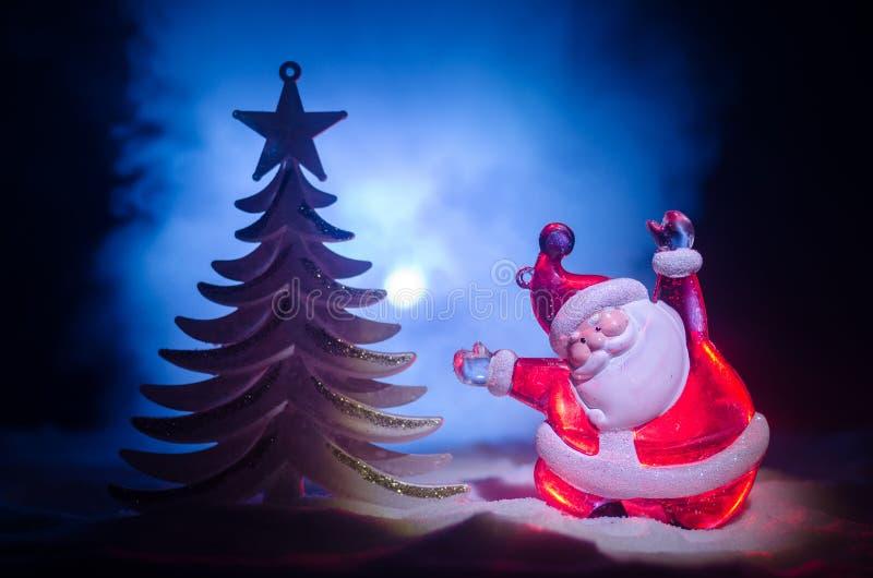 Santa Claus Doll feliz el tiempo de la Navidad con el árbol y la nieve Fondo colorido del bokeh Higo del modelo de Papá Noel y de fotos de archivo libres de regalías