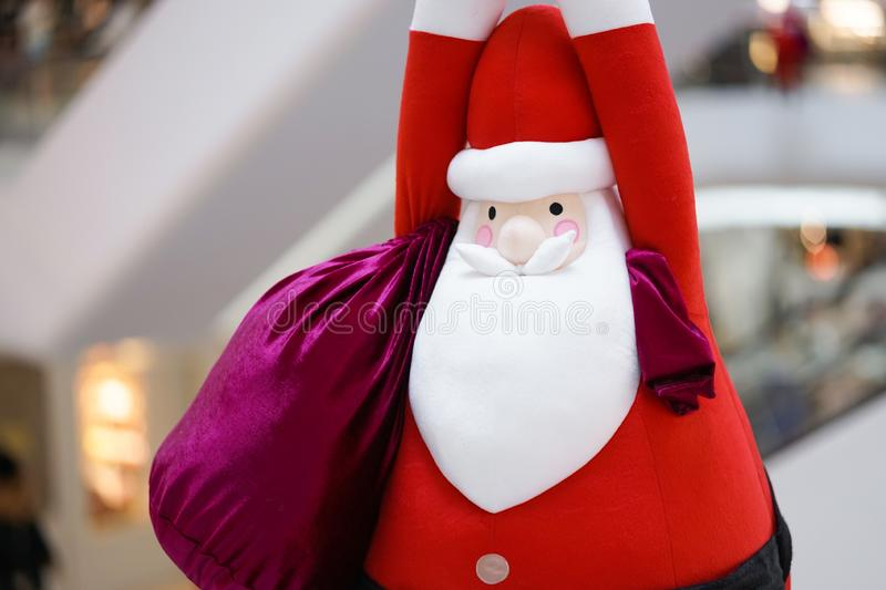 Santa Claus doll. A giant Santa Claus soft plush doll is hanging down from the ceiling with a big bag of present inside stock photos
