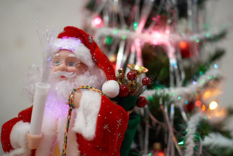 Santa Claus doll with gifts in front of blurred Christmas tree on the background.  stock photo