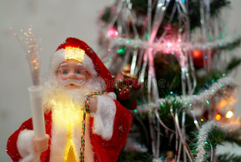 Santa Claus doll with gifts in front of blurred Christmas tree on the background.  stock photos
