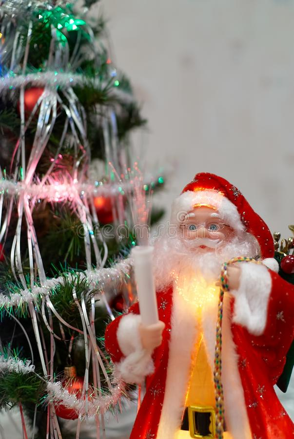 Santa Claus doll with gifts in front of blurred Christmas tree on the background.  stock images