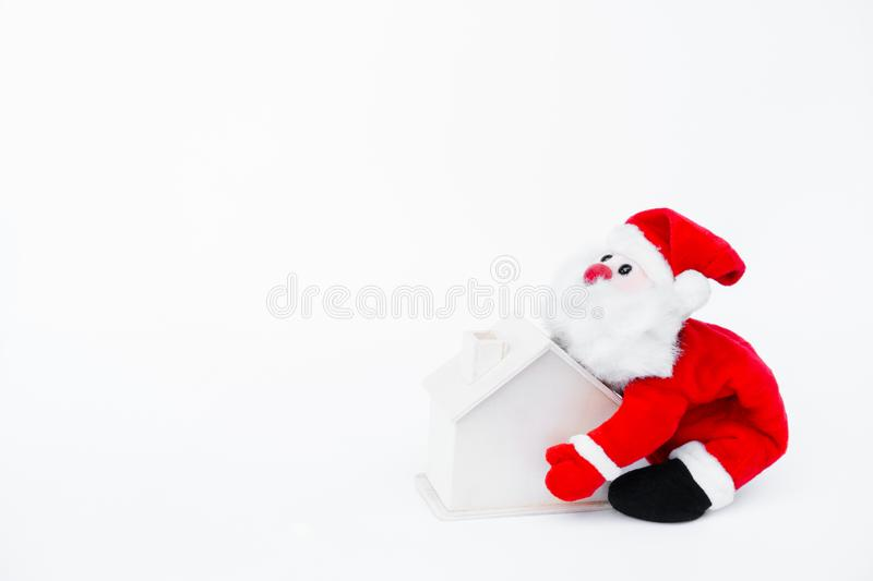 Santa claus doll holding a small wooden house on isolated on white background,Christmas decoration. Santa claus doll holding a small wooden house on isolated on stock image