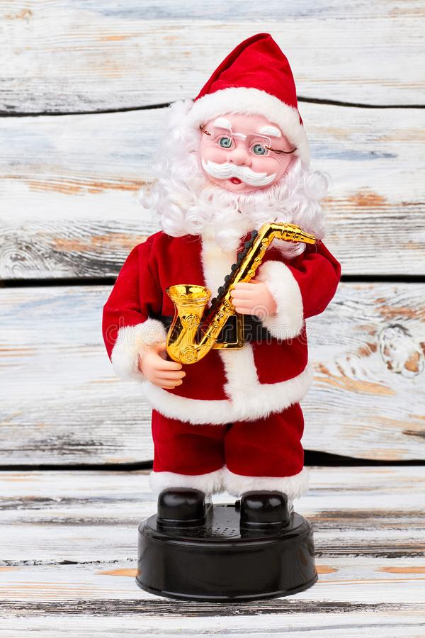 Santa Claus doll with saxophone. Musical toy Santa Claus with golden saxophone standing on rustic wooden background. Symbol of Christmas and New Year royalty free stock photos