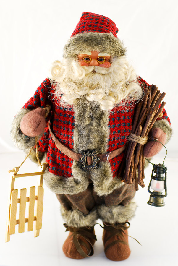 Santa claus doll with sledge. Santa claus doll isolated on white with wood and sledge in his hand stock photo