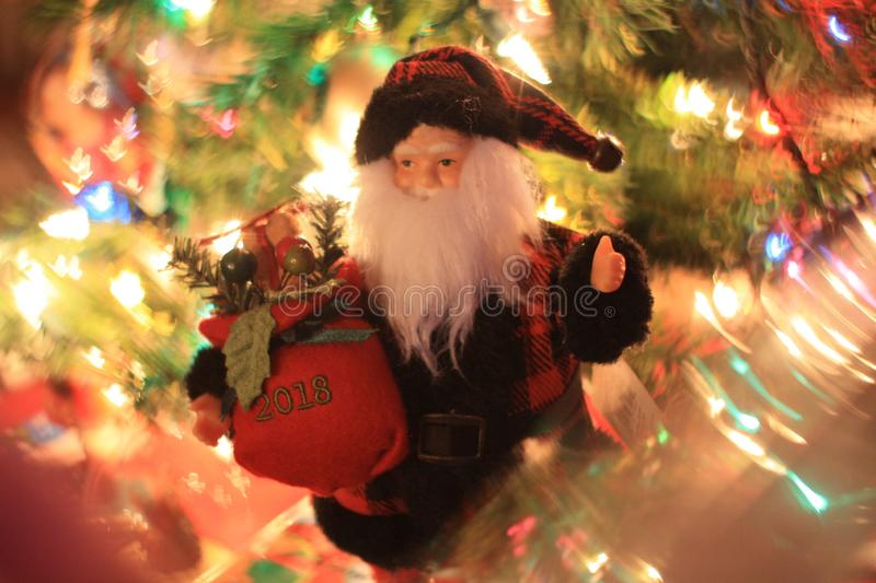 Santa Claus Doll w Dove Bokeh. My Santa Doll beneath my Christmas tree by the presents with dove shaped bokeh shot on my 50mm prime lens. Using trendy glass royalty free stock image
