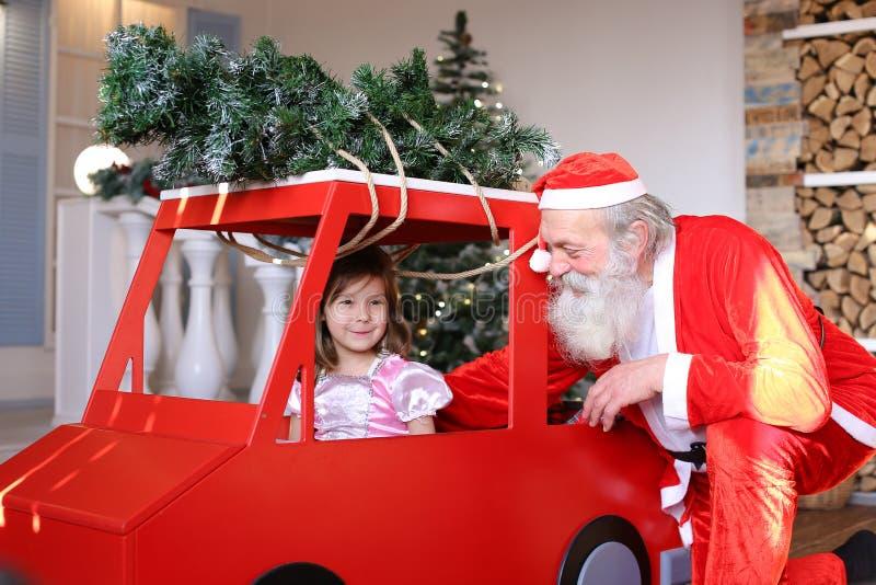 Santa Claus drôle jouant avec de petits princes ondulant la main en rouge images stock