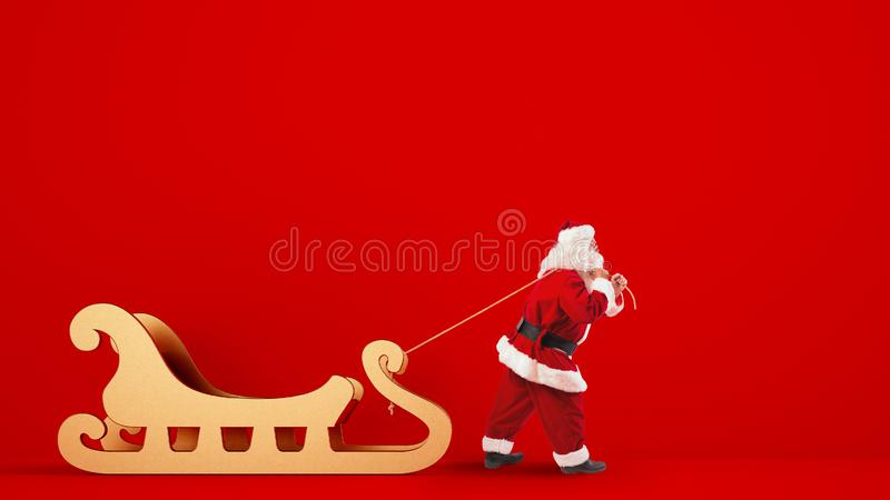 Santa Claus drags a big golden sleigh on a red background stock photos