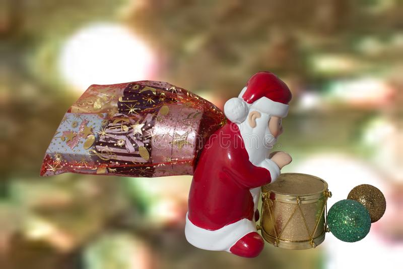 Santa Claus with drum and gifts. Santa Claus with a drum and a bag full of presents on a Christmas background royalty free stock photo