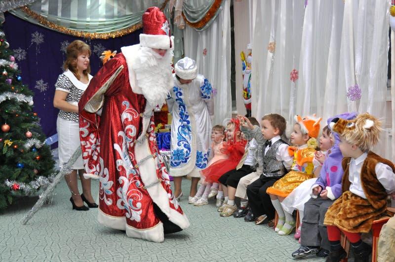 Santa Claus e a fala nova da neve com crianças fotografia de stock royalty free