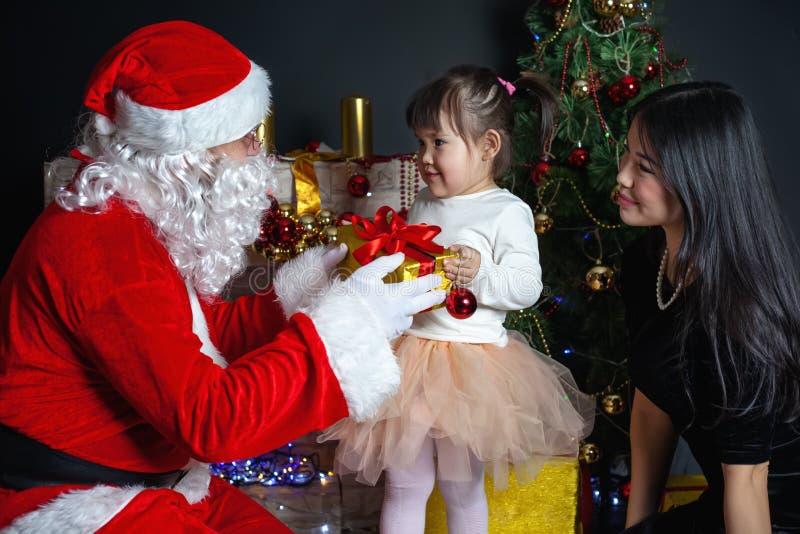 Santa Claus e madre con il vostro bambino in un vestito Scene di Natale fotografia stock