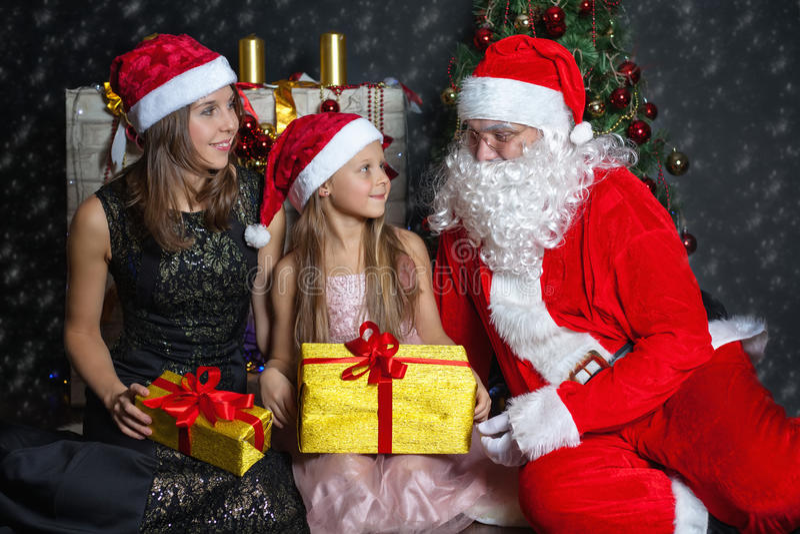 Santa Claus e madre con il vostro bambino in un vestito Scene di Natale immagine stock libera da diritti