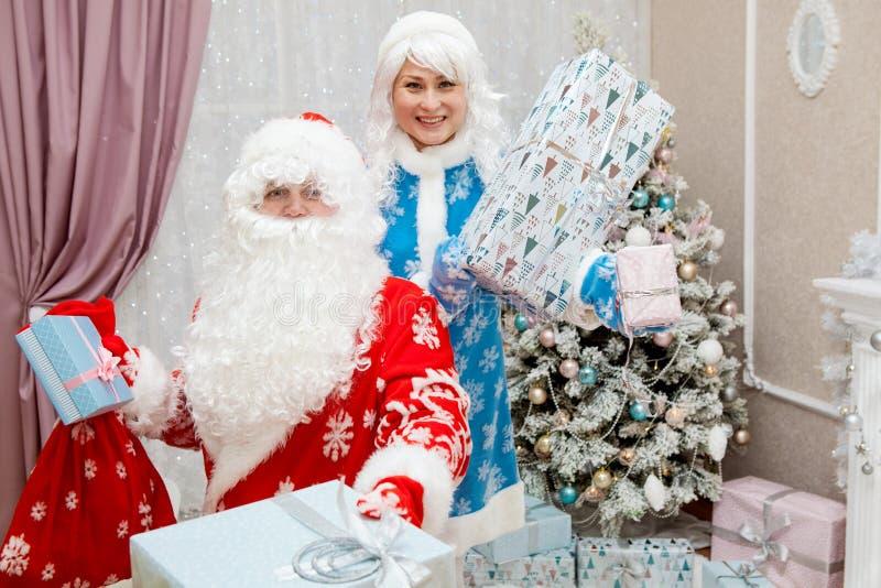 Santa Claus e nipote con i regali del nuovo anno in loro mani ` S del nuovo anno e Natale immagine stock libera da diritti