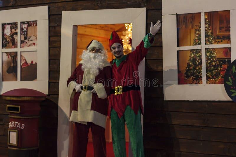 Santa Claus e o duende estão cumprimentando na porta da casa de Santa imagem de stock