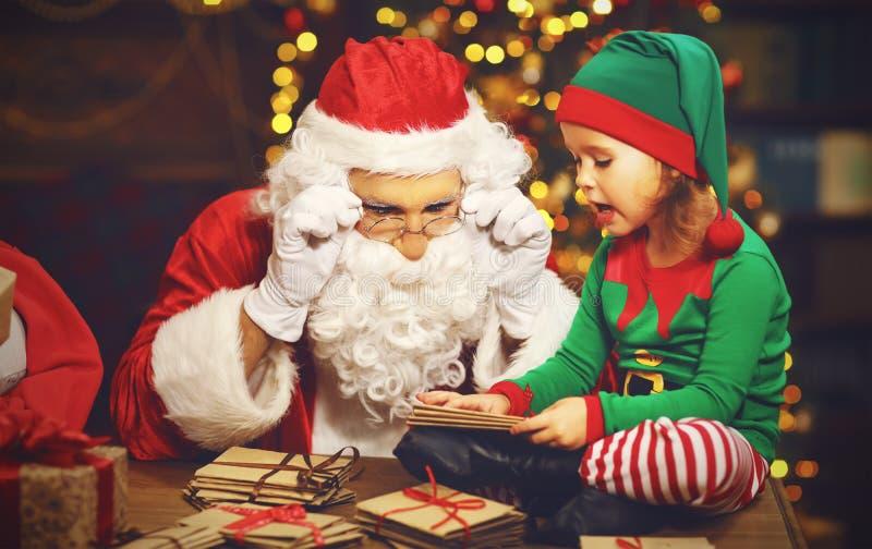 Santa Claus e un bambino dell'elfo in Natale lavorare, leggente lett fotografia stock