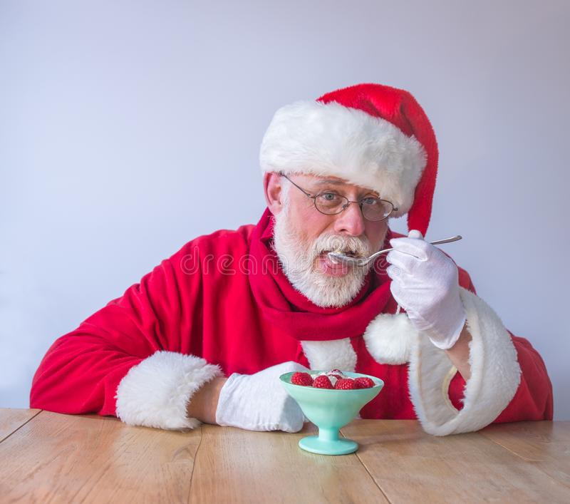 Santa Claus eating fresh raspberries. Healthy natural food concept royalty free stock image