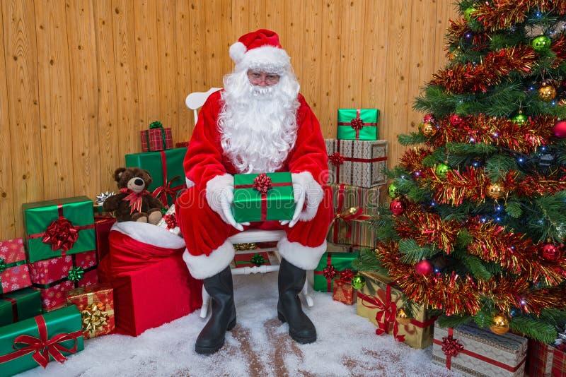 Santa Claus in einer Grotte, die Ihnen ein Geschenk gibt stockbild