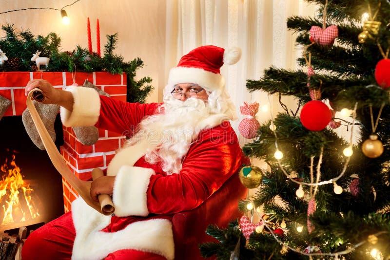 Santa Claus in einer Weihnachtsliste mit einem Geschenk in den Händen von lizenzfreies stockfoto