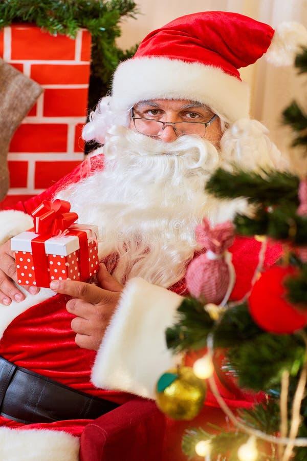 Santa Claus em sua cadeira com um presente nas mãos de um close-up foto de stock royalty free