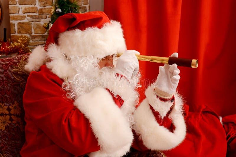 Santa Claus em sua casa, guardando o telescópio pequeno, preparando-se para o curso foto de stock