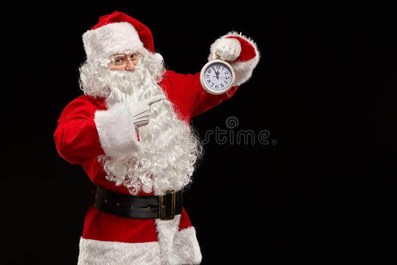 Santa Claus em um fundo do preto aponta seu dedo no pulso de disparo Conceito do Natal fotografia de stock royalty free