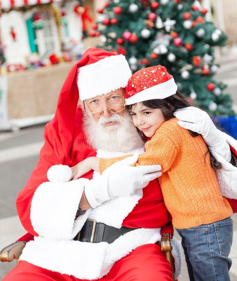 Santa Claus Embracing Girl imagens de stock