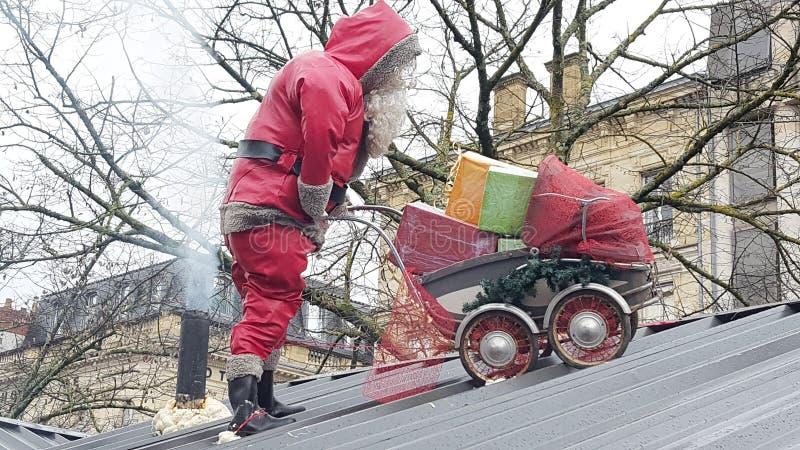 Santa Claus empurra um pram enchido com o presente em um telhado com uma chaminé fotos de stock