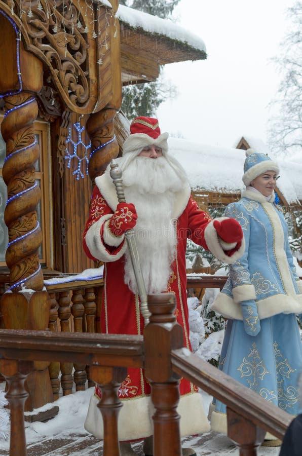 Santa Claus en het Sneeuwmeisje gaan op het terras van hun manor in de winter uit tegen de achtergrond van snow-covered stock foto's
