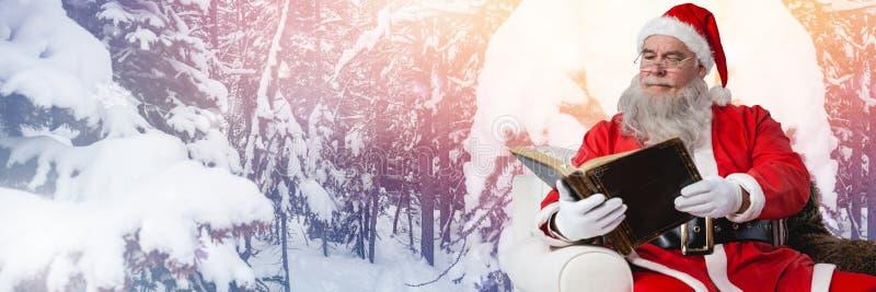Santa Claus en hiver avec le livre images stock