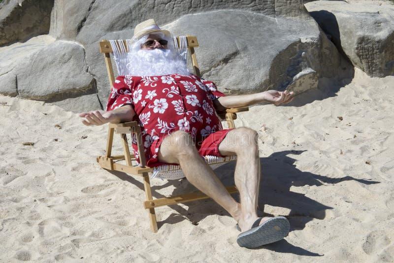 Santa Claus en la playa soleada fotos de archivo