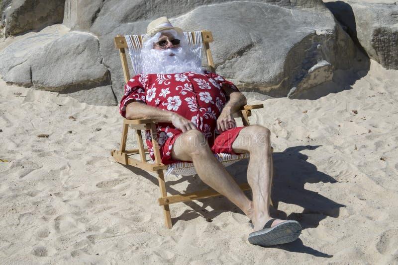 Santa Claus en la playa soleada en silla fotografía de archivo libre de regalías
