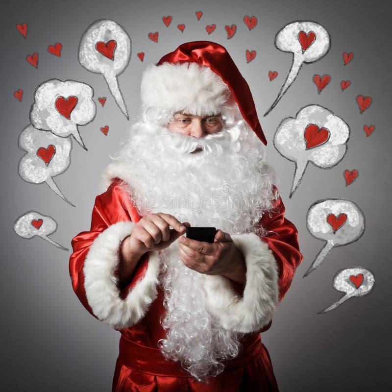 Santa Claus en slimme telefoon Het concept van de liefde stock foto's