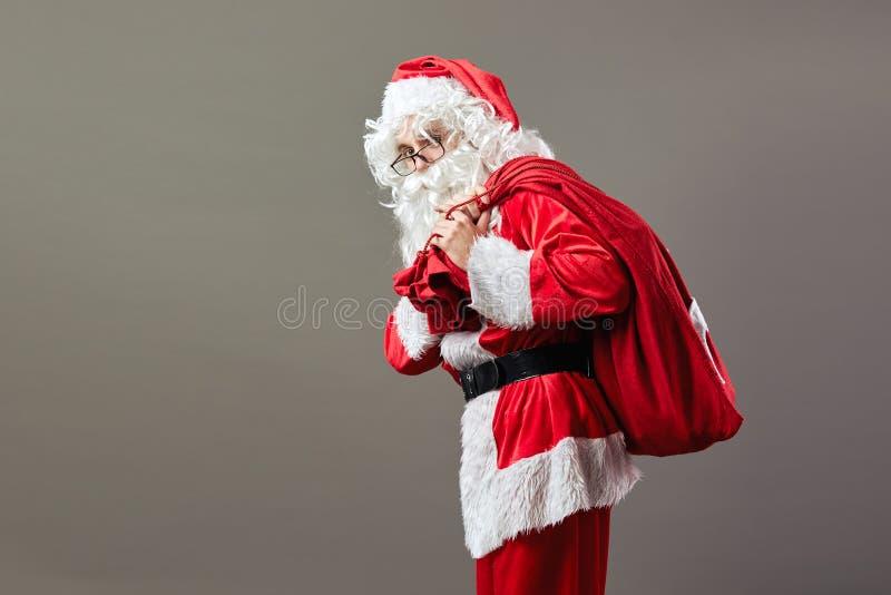 Santa Claus en soportes de los vidrios con el bolso con los regalos de la Navidad en el suyo detrás en el fondo gris imagenes de archivo
