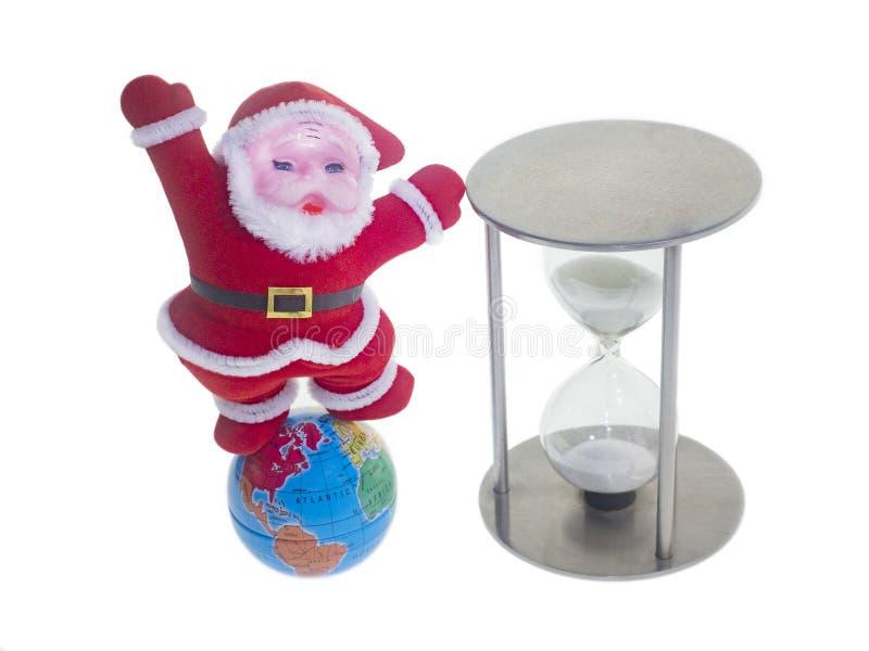 Santa Claus en un traje rojo tradicional, globo, reloj de arena aislante foto de archivo libre de regalías