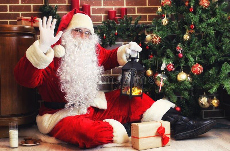 Santa Claus en un traje rojo y una barba blanca en el árbol de navidad imagen de archivo