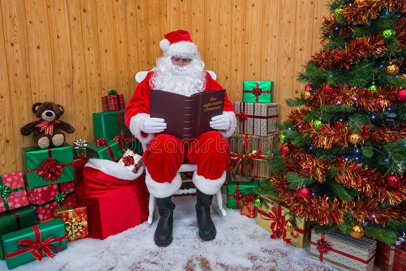 Santa Claus en una gruta que lee su libro de la Navidad fotos de archivo libres de regalías