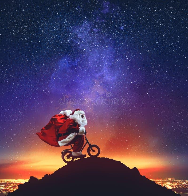 Santa Claus en una poca bici en el pico de una montaña debajo de las estrellas imagen de archivo libre de regalías