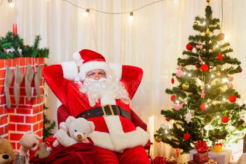 Santa Claus en una silla en el cuarto con el árbol de navidad y la f fotos de archivo