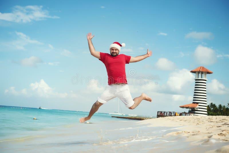Santa Claus en wenst een gelukkig nieuw jaar De grappige sprongen van de Grootvadervorst op het overzees royalty-vrije stock afbeelding