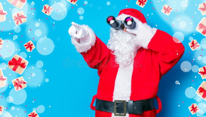 Santa Claus engraçada tem um divertimento com binóculos imagem de stock