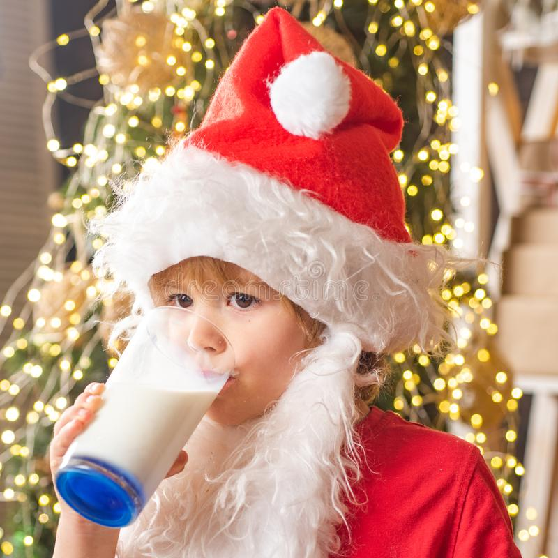 Santa Claus enjoys cookies and milk left out for him on Christmas eve. Merry Christmas. Santa picking cookie and glass. Of milk at home. Santa picking cookie stock photography